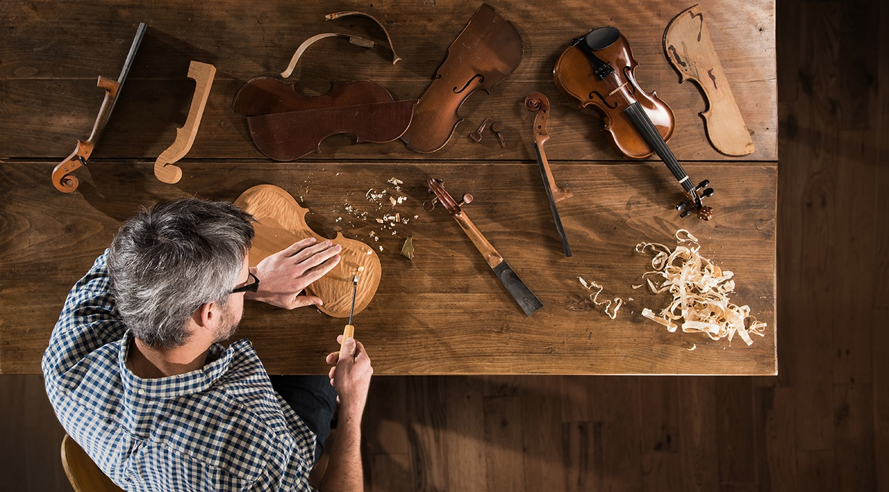 vue de dessus d'un luthier au travail