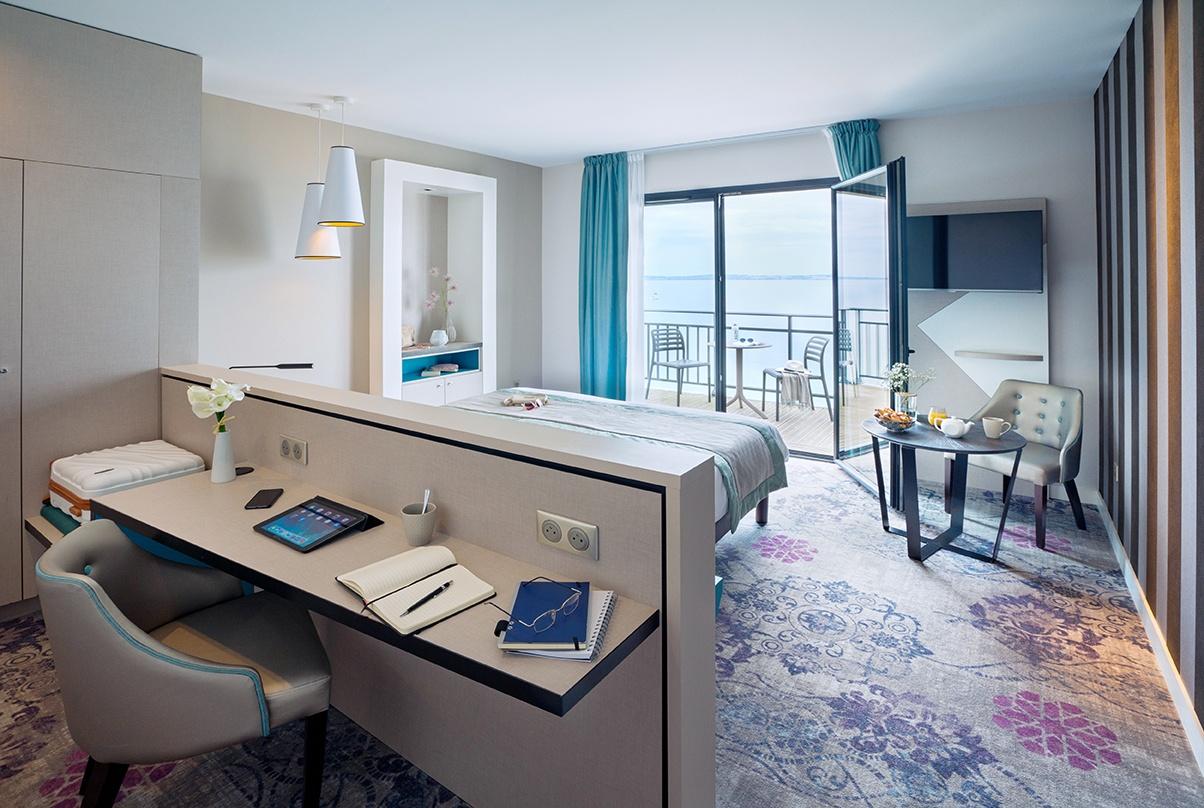 ambiance d'une chambre d'hôtel avec terrasse vue mer