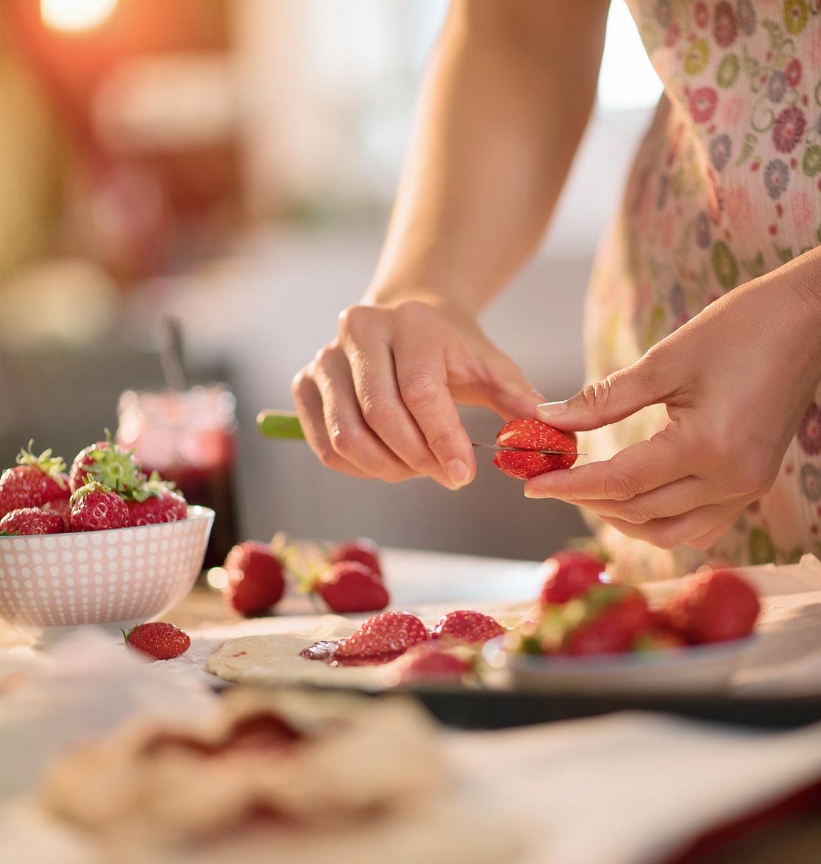 image des mains d'une femme préparant une tarte aux fraises