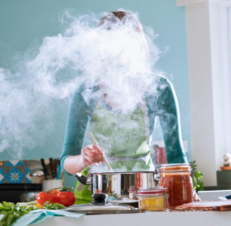 photo lifestyle d'une cuisinière derrière ses fourneaux