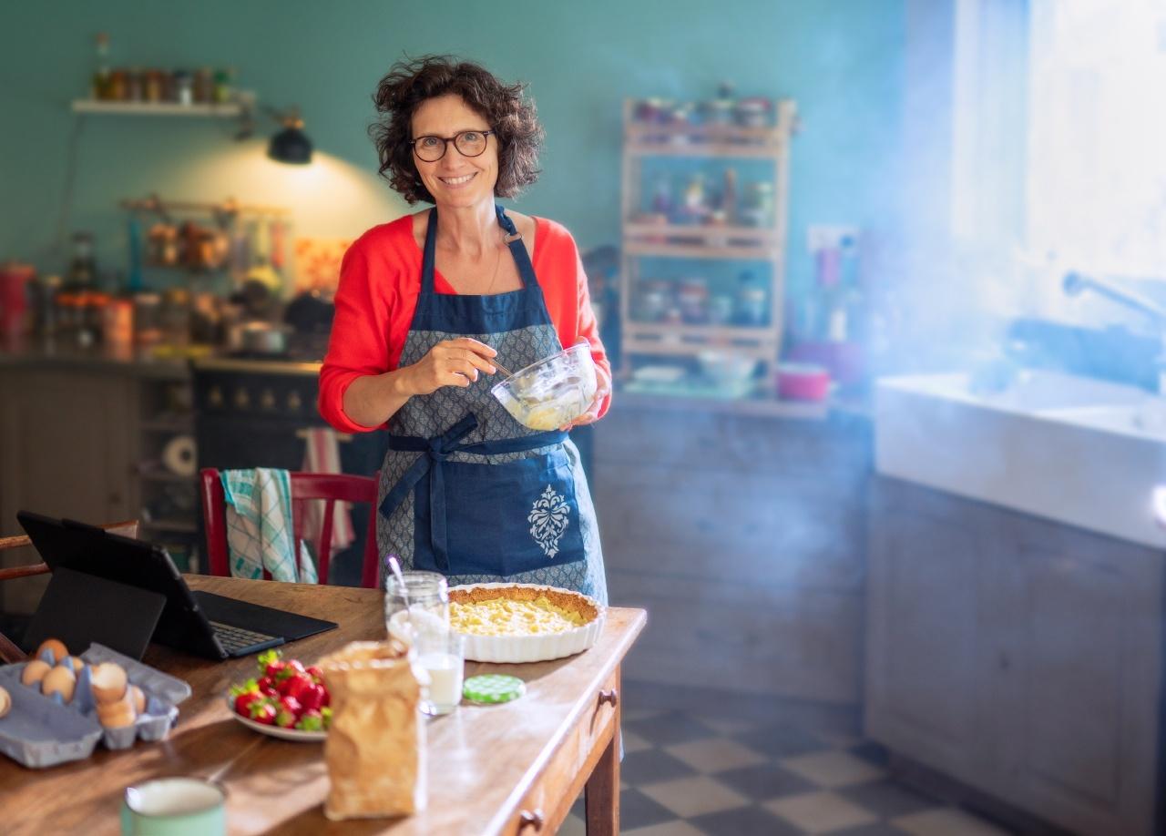 photo lifestyle d'une femme faisant une tarte dans sa cuisine