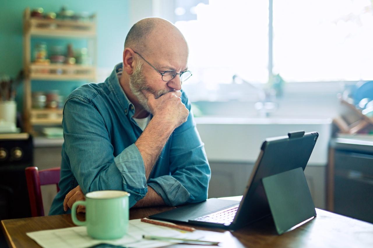 Image lifestyle d'un homme senior devant son ordinateur dans sa cuisine