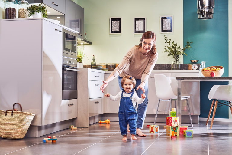 Photo lifestyle d'une maman et son bébé qui commence à marcher dans la cuisine
