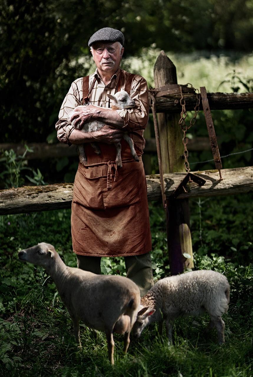 Photo d'un eleveur de mouton avec un agneau dans les bras