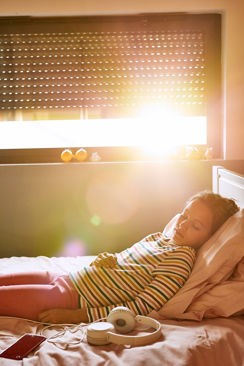 Photo d'une enfant dormant écoutantde la musique sur son lit avec un casque